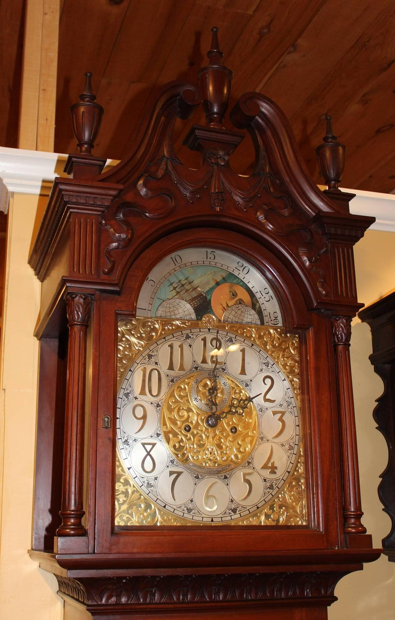 An exceptional mahogany tall case clock with single tubular chime, along with a ribbon carved bonnet with swan's neck broken pediment, three urn finials, freestanding fluted columns flanking the dial door, 13 inch chased brass dial with applied