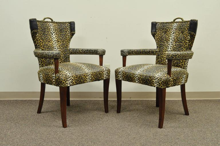 Pair of 1950s Hollywood Regency cheetah or leopard printed vinyl curved back armchairs attributed to Dorothy Draper. Item features mahogany wood frames, brass handles, curved backs, nailhead trim, and great form.