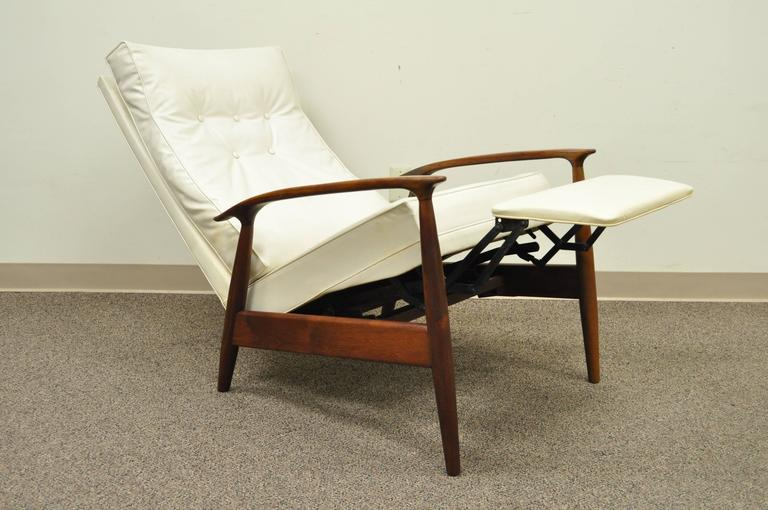 Early Milo Baughman designed sculpted frame reclining walnut lounge chair for James, Incorporated (An early division of Thayer Coggin). Chair features a very comfortable reclining position with flip out footrest and the original white vinyl