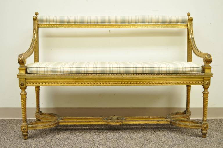 Very unique French giltwood bench in the Louis XVI taste. Item features an ornate stretcher supported base, swirl reeded legs, open back, cane seat, lose cushion, upholstered upper rail and elegant French form.