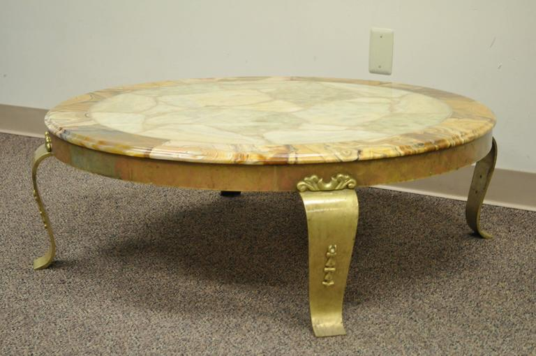 Stunning Hollywood Regency / Mid-Century Modern round coffee table by Muller. Item features a solid brass base with decorated scrolling cabriole legs and a beautiful onyx top with beveled edge. Brass is in original condition and has achieved a