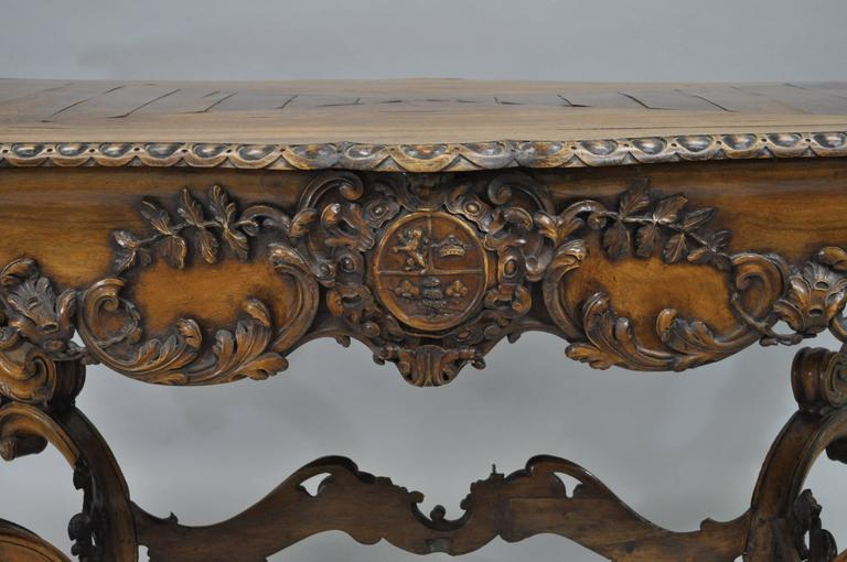 Ornate early 19th century Italian baroque carved walnut center table in the French Louis XV taste. Table features an impressive overall form with fine carvings throughout including the shapely acanthus form legs, stretcher base, plank inlaid walnut