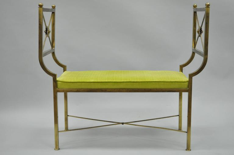 Very unique vintage brass X-Form bench in the Regency style. This item features an X-form stretcher base, clean lines and a burnished brass finish.