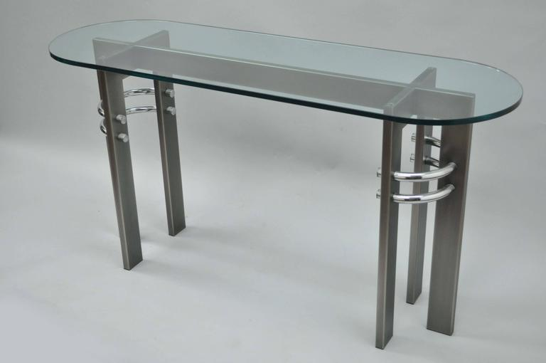 Contemporary or Memphis style brushed metal, chrome and glass console table design institute of America dia. Item features a thick oval glass top and unique sculptural base.
