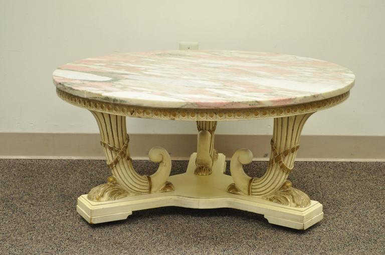 Vintage French Empire / Neoclassical style marble top coffee table. Item features a triple cornucopia carved wood base, pink round marble-top, off white original painted finish and rolling casters.