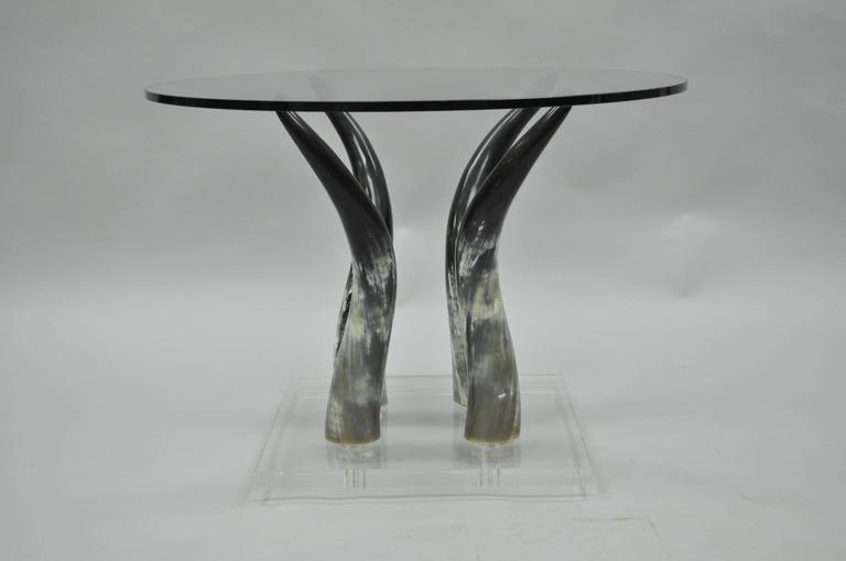 Very unique vintage Mid-Century Modern Lucite, glass and Horn occasional side table. Item features a round glass top, four faux Horn supports raised on a Lucite floating form base.