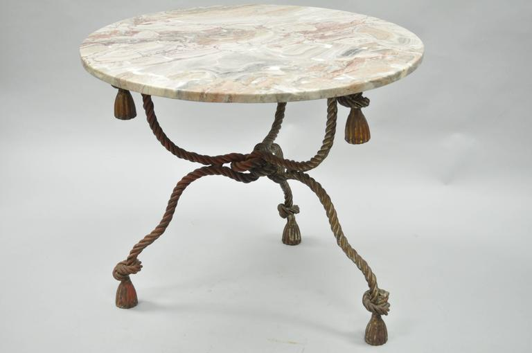 1940s Italian Hollywood Regency marble-top rope turned center table. Item features a pink accented round marble top, heavy rope and tassel form iron base with a desirable antiqued gold gilt finish. Stunning quality item. Stamped, made in Italy.
