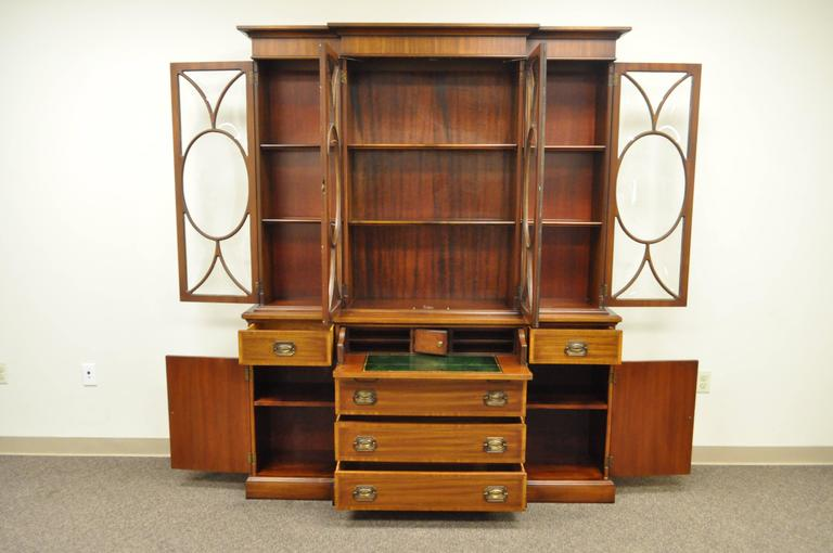 Exceptional 1940s English Georgian style custom bubble glass two-piece mahogany breakfront. This bookcase features individual panes of bubble glass, drop front writing desk surface with green tooled leather top, banded and satinwood inlays with