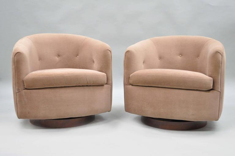 Pair of authentic Milo Baughman for Thayer Coggin swivel walnut base barrel back club chairs. This pair of Mid-Century Modern lounge chairs features rounded backs and walnut veneer swivel plinths.