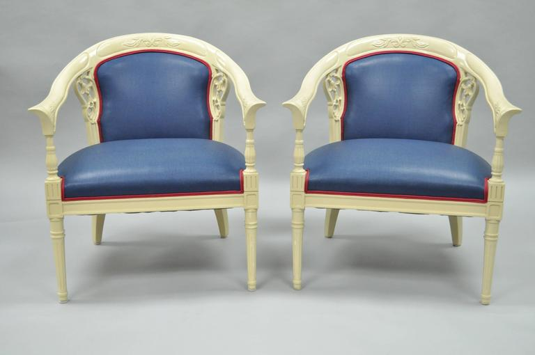 Elegant pair of vintage Hollywood Regency barrel back armchairs in the French style. Item features shapely rounded frames, bell flower pierce carved backrests, rolled and flared arms, tapered legs, cream lacquered finish and blue fabric with reddish