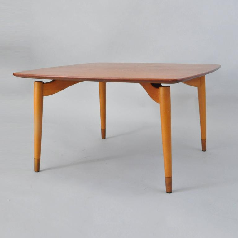 Unique floating form vintage Danish Modern square coffee table by Poul Jeppesen with the design attributed to Grete Jalk. Item features a square teak wood top with rounded corners and four floating form sculptural tapered legs. Very clean modernist