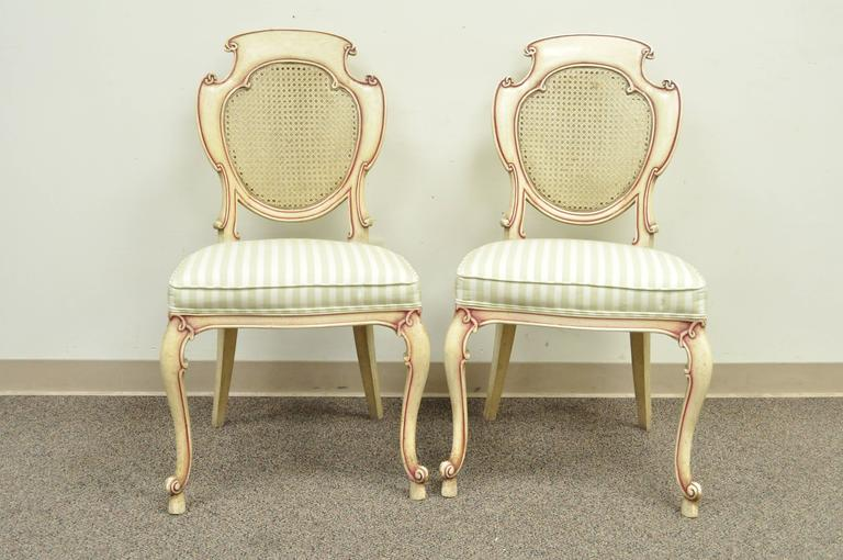 Very unique set of four vintage scroll carved Italian Hollywood Regency cream and pink painted side chairs. Chairs feature carved solid wood frames, caned backs, cabriole legs in the French style, and upholstered seats. Each back is scroll carved