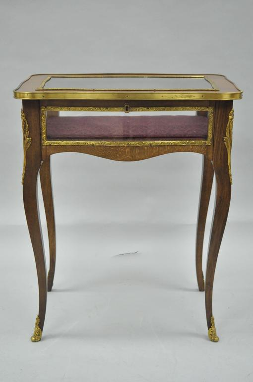 """Attractive vintage French Louis XV style flip-top display accent table. Item features cast brass ormolu, glass flip-top, glass sides, shapely cabriole legs, and upholstered interior. Marked """"Made in Spain"""" on underside."""
