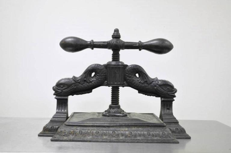 Very unique and historically important antique cast iron dolphin book/copy press. The piece features intricate supports with dolphins and fluted columns, and acanthus accented base. The press is very substantial and heavy, and though it does not