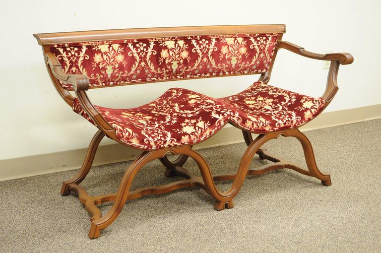 Unique vintage Hollywood Regency double Curule X-form Savonarola style bench. Item features a solid walnut carved wood frame, stretcher base, double curved seats, red textured floral printed upholstery, and great quality and construction.