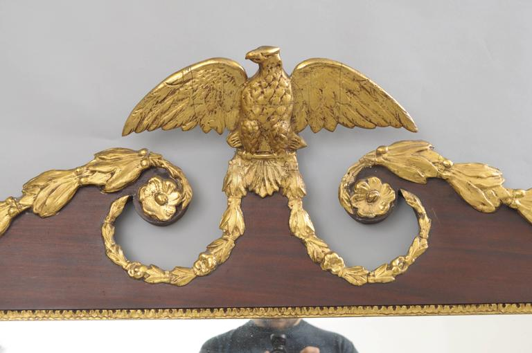 A horizontally oriented three-panel mahogany overmantel mirror with scrolling pediment centred with a mounted eagle finial with open wings and accented with a gold giltwood and gesso floral swag border with rosettes at the corners and pediment.