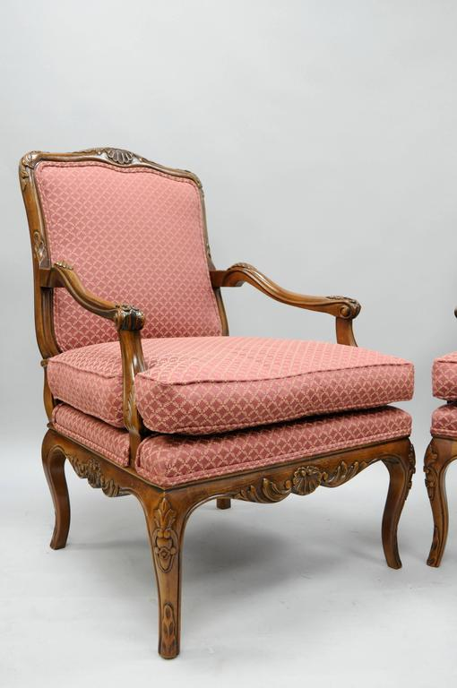 Pair of 20th century, high quality, country French / Louis XV style shell carved living room lounge chairs by Century Chair Company. The pair features solid carved wood frames, deep comfortable seats, finely carved skirts with shell and floral