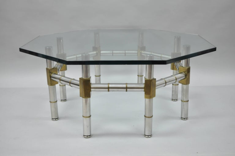 Vintage Mid-Century Modern / Hollywood Regency octagonal chrome and brass faux bamboo coffee table in the manner of Maison Jansen. Item features a unique brass and chrome faux bamboo style frame, .75
