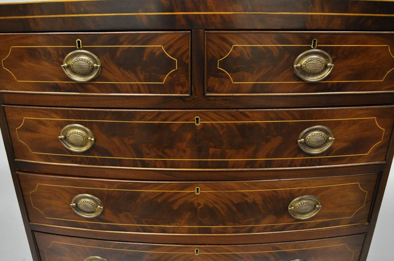 Antique mahogany American Federal inlaid five-drawer chest. Item features beautiful flamed / crotch mahogany veneers, satinwood pencil inlay, five dovetailed drawers, bow front, brass hardware, panel wood backing, all drawers have locks which are