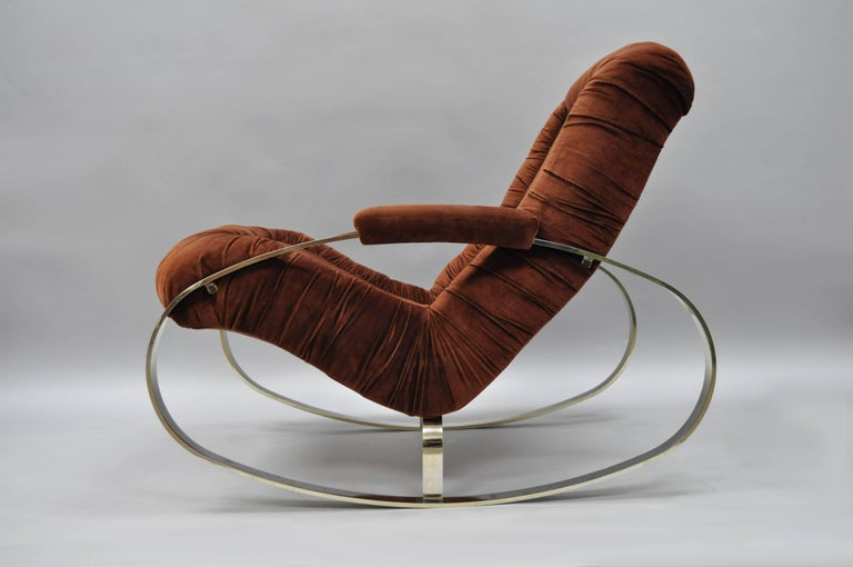 Vintage Italian Mid-Century Modern steel frame rocking chair by Guido Faleschini. Item features a heavy ovoid shaped steel frame with chrome/bronze finish, upholstered armrests, and original rust color fabric.