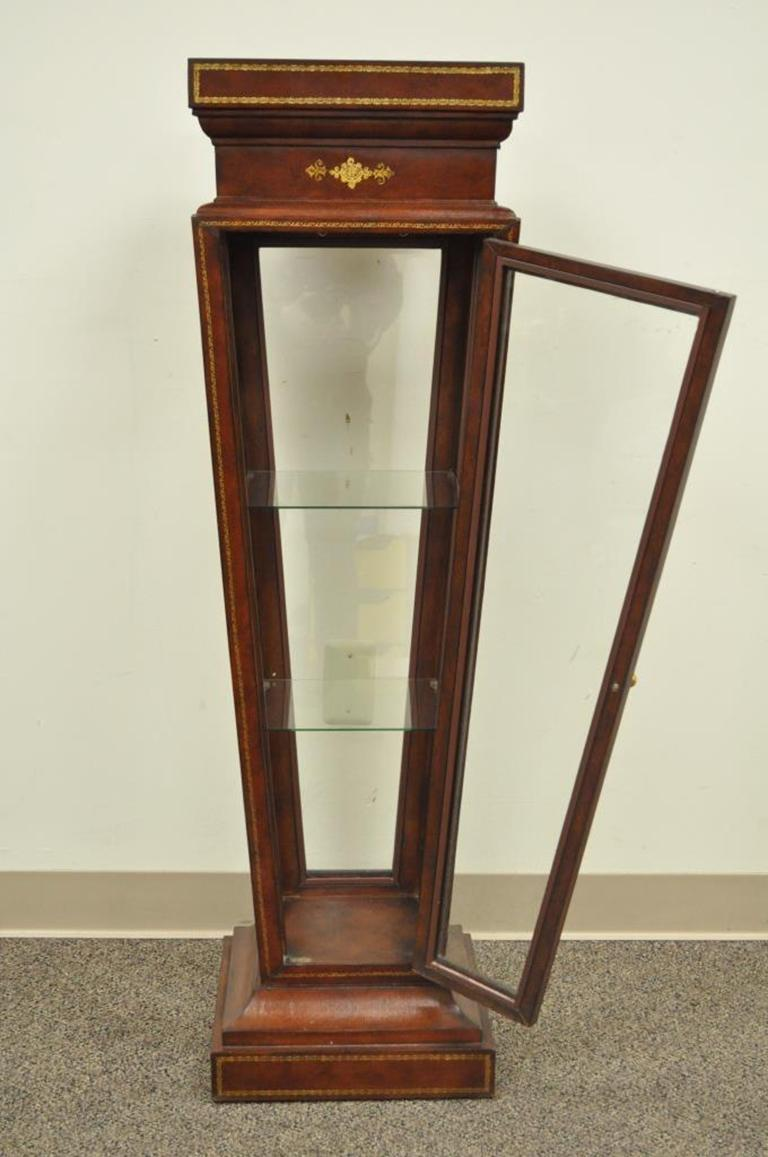 Unique leather wrapped pedestal or curio. Item features clear glass display case base with swing door, two interior glass shelves, beautiful tooled leather wrapped frame with gold gilt detailing, the maker is unconfirmed but possibly Maitland-Smith,