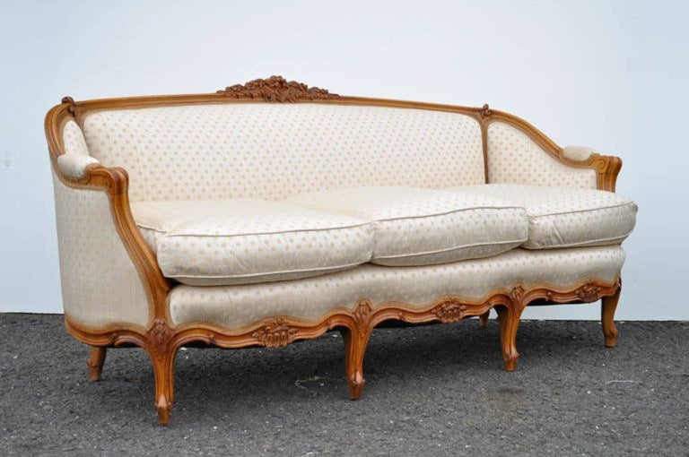 Gorgeous vintage French Louis XV style carved walnut sofa. The item features beautifully carved floral accents, scroll work arms, and six cabriole legs, as well as a nice beige and gold clover patterned upholstery and down filled cushions.