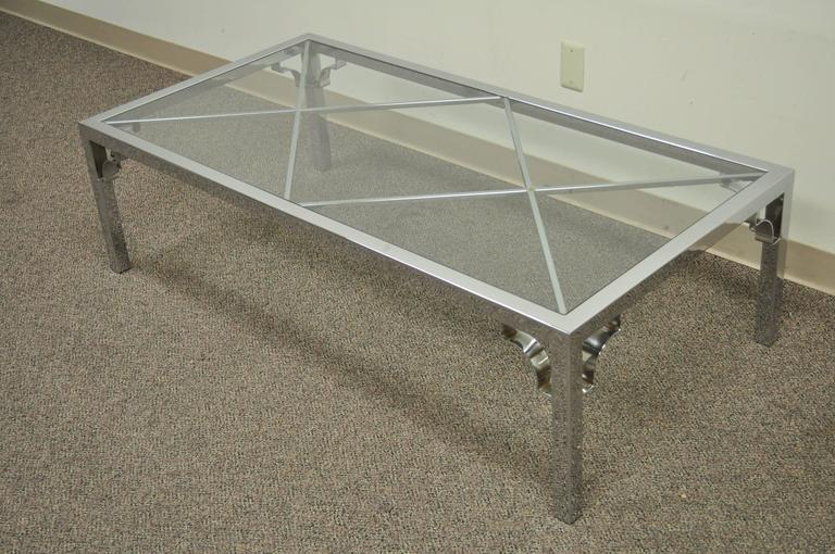 Wonderful vintage coffee table with polished chrome frame and double X-forms under the inset glass top. This table features polished seamless joints throughout for a more clean overall aesthetic. Each leg has decorative arched detailing at the