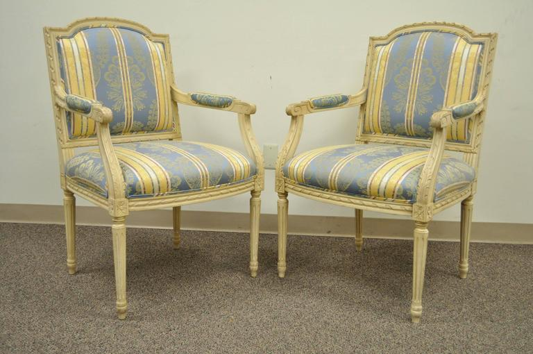Pair of 20th Century French Louis XVI style armchairs with finely carved floral and ribbon form accents, scroll form arms, and reeded and tapered column form legs. The chairs are upholstered in an absolutely lovely blue and yellow striped fabric