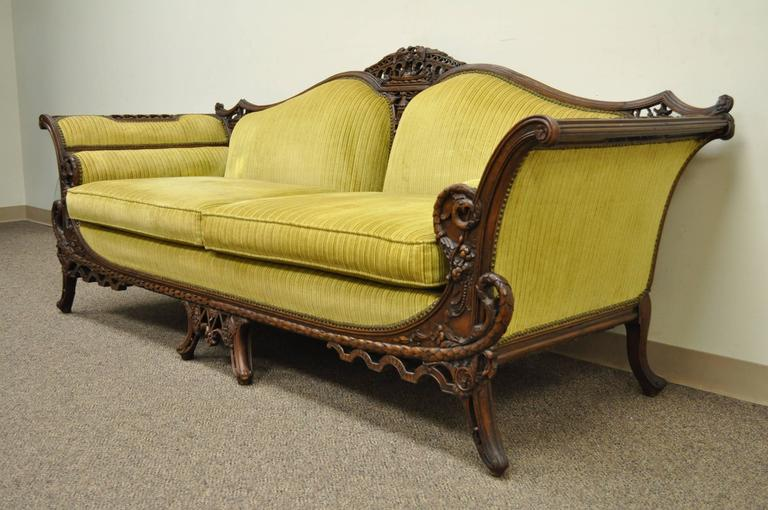 Remarkable, hand-carved, Mahogany sofa from the early 20th century in the transitional Chinese Chippendale style. Item features a number of very fine and detailed carvings including, birds, serpents, swan heads, cornucopia, pagodas and other flowers