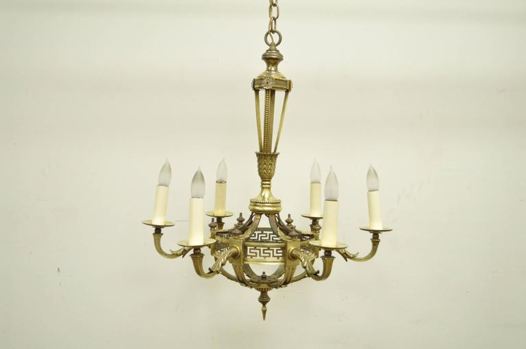 Elegant French neoclassical style, six-light, bronze chandelier. Item features a basket form frame, glass floral medallions at the top of the central shaft, cast bronze acanthus detailing and pierced Greek Key designs around the basket.