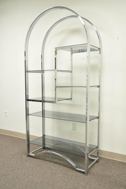 Striking arched chrome vintage etagere or bookcase in the style of Milo Baughman. In addition to its sleek modern form the piece boasts 6 smoked glass shelves of varying sizes.
