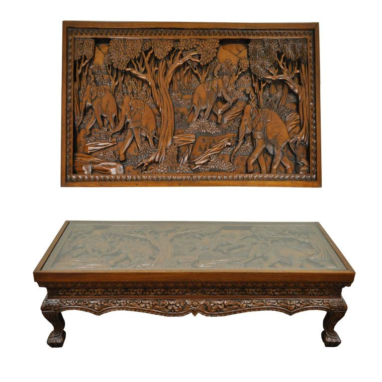Inset glass top deep relief carved Vietnamese low table. Heavily carved throughout depicting elephants working in a forest. Very nicely done with figural carved legs/feet and floral acanthus carved skirt. Believed to be solid teak wood or solid