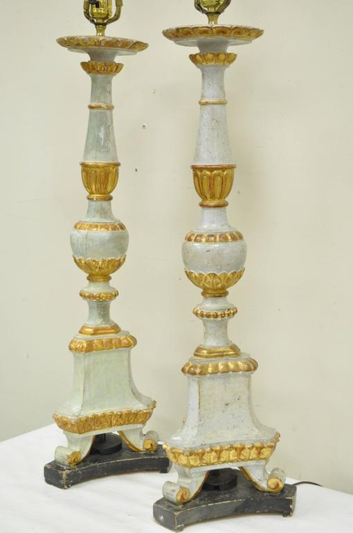 Pair of early 20th century Italian hand-carved solid wood parcel-gilt neoclassical style table lamps. Original Italian label found on the top of the lamps. Lamps have remarkable old world character with signs of desirable age to the wood as