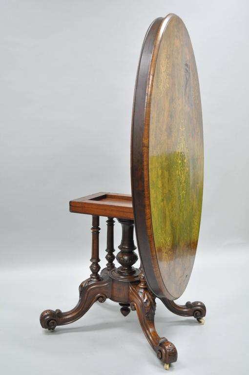 Victorian walnut tilt-top center table, circa late 19th century. The oval burl wood top, inlaid with floral marquetry, rising on four turned supports with a carved central shaft, foliate carved outswept curved legs on scroll feet and casters. 62
