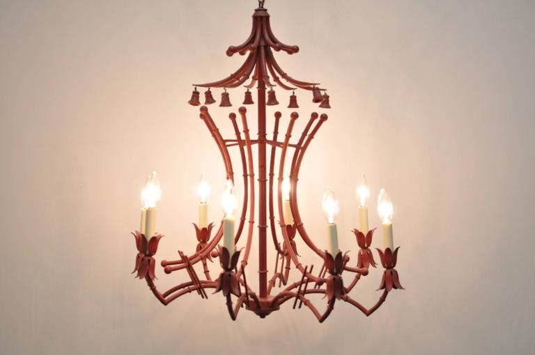 Fabulous vintage red painted Italian faux bamboo tole metal chandelier. Item features a unique pagoda frame with non-ringing bell accents, eight arms and lights, and Classic Chinese Chippendale form.