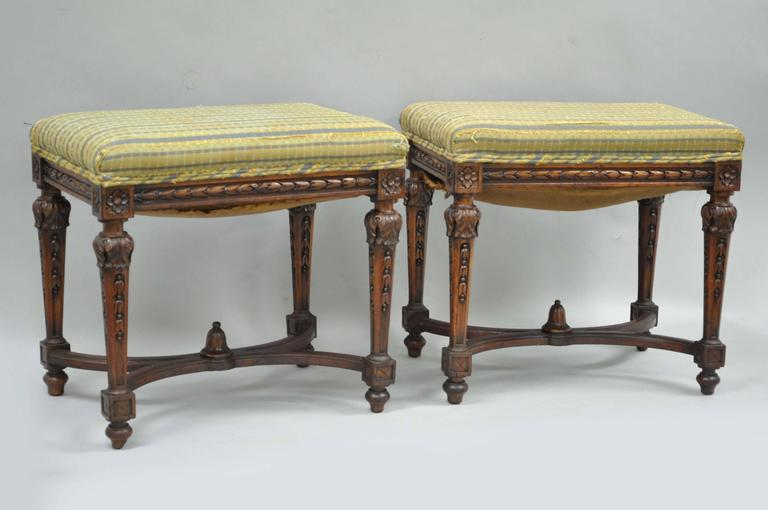 Quality pair of antique Victorian carved walnut French Louis  XVI style benches or stools with carved stretcher bases. Stools feature medallion, bell flower and acanthus carved frames with elegant and Classic form.