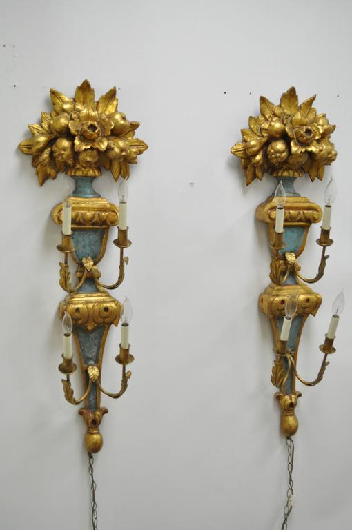 Pair of 1950s carved giltwood Italian style four-light wall sconces, made in Spain by Masa. Item features four iron arms each with four electrified lights, painted and gilt finish, carved wood floral and fruit bouquet toppers and stately size and