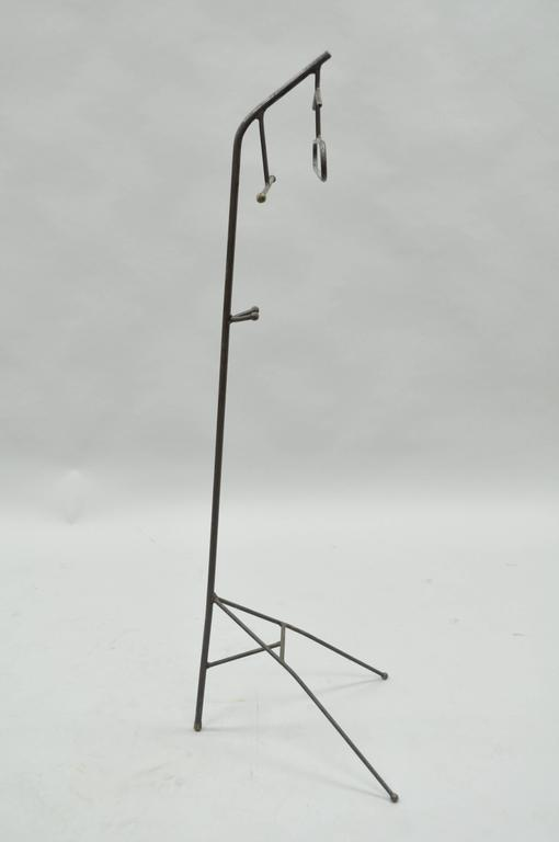Unique vintage French Mid-Century Modern wrought iron and brass hairpin clothing or clothes valet in the manner of Jacques Adnet. Item features brass ball ends on the iron rods, clean modernist lines and great form. Item is constructed primarily of