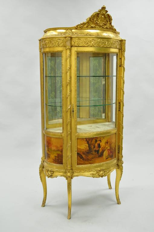 Remarkable Late 19th century French Louis XV style gold giltwood vernis Martin curved glass curio cabinet. The French cabinet, with serpentine top and case, carved with tied ribbons, husks and leafy vines, with mirrored interior and curved glass
