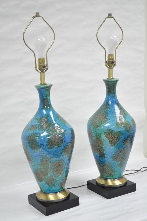 Remarkable pair of quality vintage blue glazed ceramic sculptural table lamps. The pair features glazed ceramic uppers resting on brass and painted wood bases with three-way sockets.