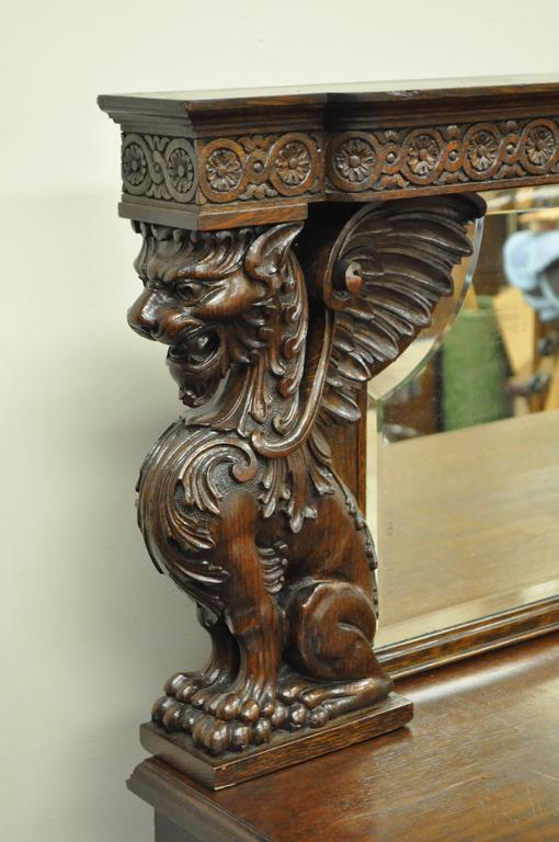 19th century Victorian Quartersawn oak figural sideboard with shaped beveled mirror. Possibly by RJ Horner NY. Item features full winged griffins and lion carved columns, beautiful quartered oak construction, paw feet, lower drop front with hidden