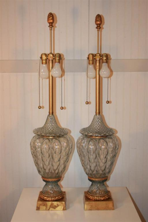 Very fine pair of large light blue tint crystal Murano glass lamps by Marbro featuring vase formed bodies, gold leaf bases, and brass ring foliage detail. Double socket, brass ball pulls, and large acorn finials all signature Marbro features. Price