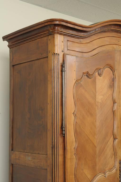 "Large and stately 93"" tall antique, 18th century, country French / Louis XV style armoire handcrafted in France of cherry and walnut wood. Item features a bonnet shaped cornice, hand-forged iron hinges, peg joined construction, two large swing doors"