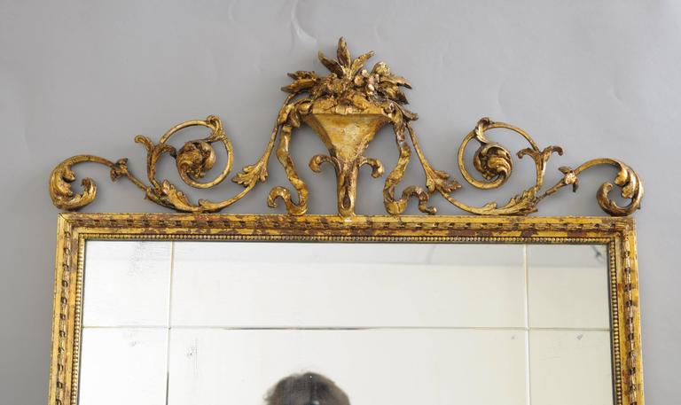 Early 20th Century carved gold giltwood and gesso English Robert Adam style rectangular wall Mirror. Item features an iron and gesso blooming floral bouquet with draping acanthus leaves and bell flowers. The giltwood and gold leaf frame displays