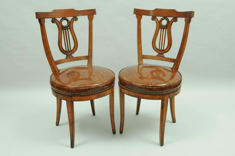 Set of four vintage lyre back regency or neoclassical style side chairs.  Chairs feature; - Set Of Four Carved Harp Lyre Back Regency Neoclassical Style Dining