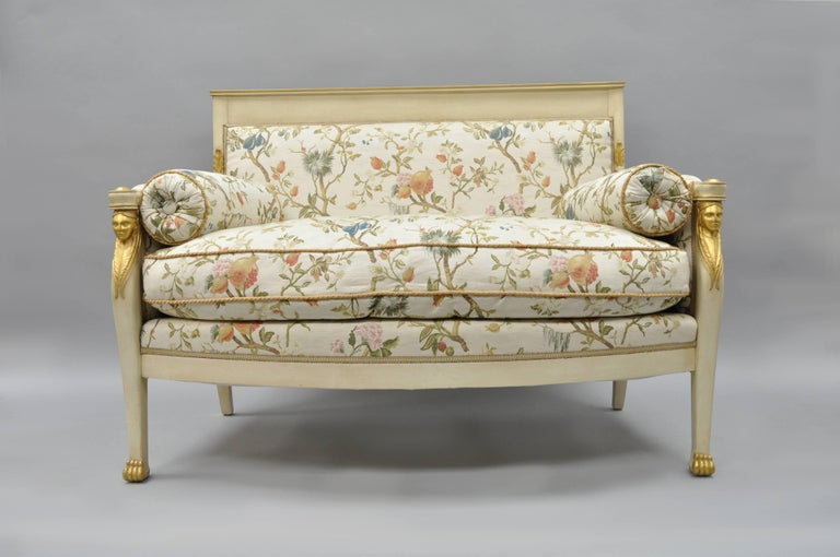 Stunning Early 20th Century French Neoclassical / Empire style figural gold gilt and cream painted settee covered in newer silk Scalamandre fabric with roped trim and down filled loose cushion. Item featured a solid carved wood frame, paw feet,