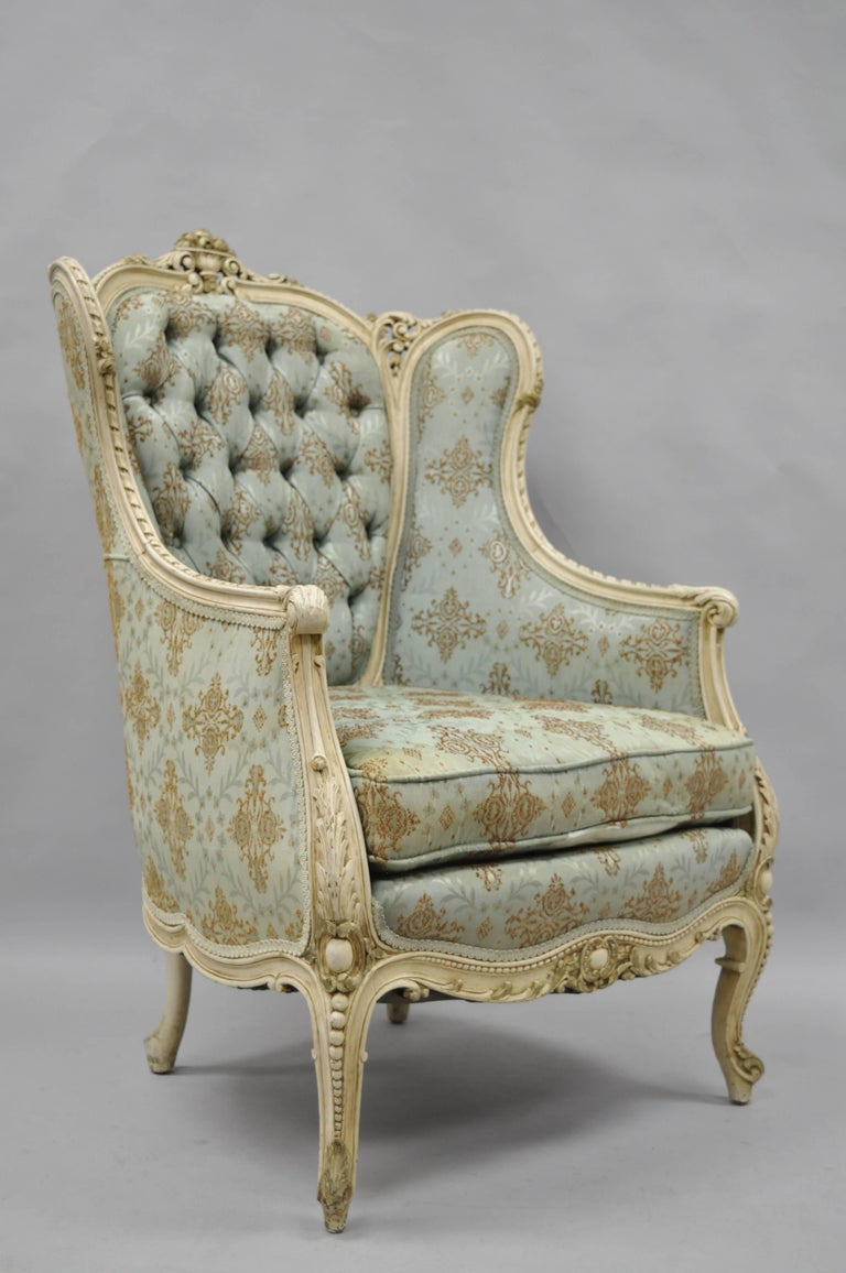 Early 1900s French Louis XV / Provincial Style Cream Painted Bergere Wing back Chair. Item features a solid carved wood frame, unique floral carved accents, cabriole legs, wing back, tufted fabric, cream painted distressed finish, and attractive