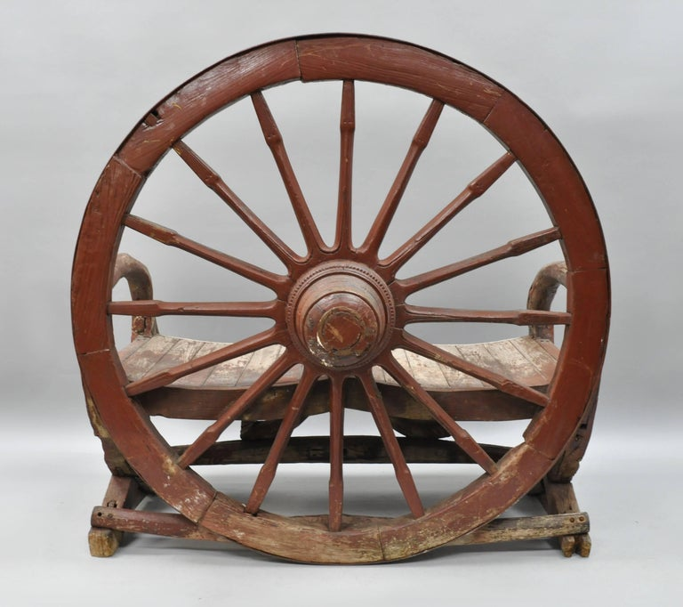 Antique primitive Conestoga wagon wheel red bench. Heavy solid wood and iron construction from an antique Conestoga wagon. Bench features the original distressed red paint, beautiful patina, two seat form, very impressive and unique item. Item