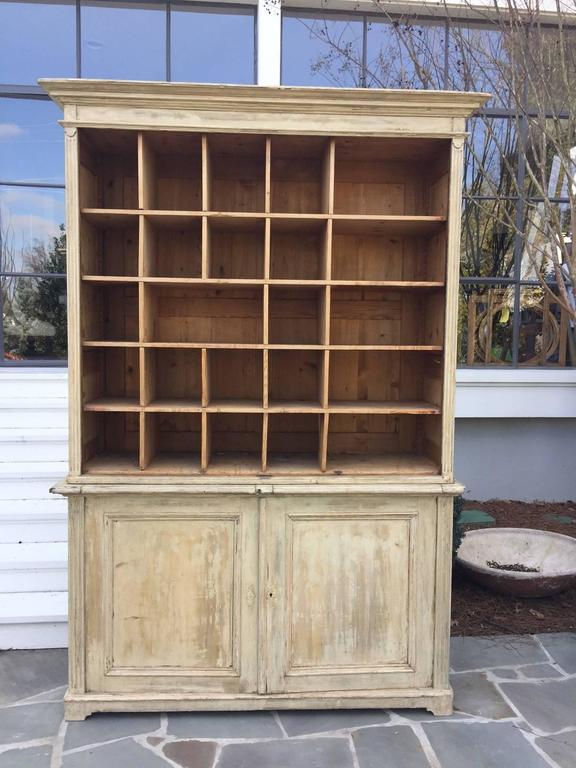 19th century French cabinet with pull out boards. This piece is in two parts and likely originated as a shop piece. The pullout boards were used to stack and sort inventory. The paint has been scarped to its original patina and it has lovely reeded