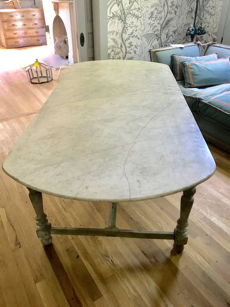 Antique French marble-top dining table with a wonderful patina. Original carved base with chamfered stretchers. Marble top has old repair and reinforced underneath wooden bracing. A beautiful and unique piece from Isle Sur La Sorgue, mid-1800s.